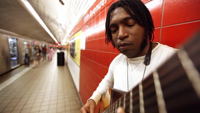 MED black man leaning against red wall plays guitar in subway station   pedestrians walk on platform