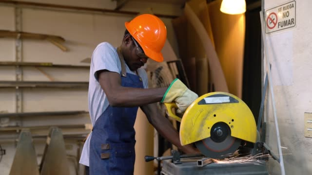 black man operating a circular saw cutting a metal bar - hand saw stock videos and b-roll footage