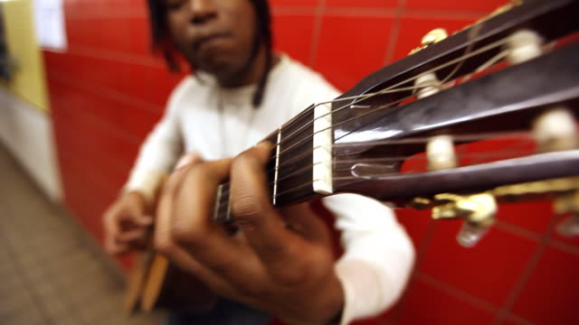 med black man playing guitar while leaning against red wall in subway station   pan up   down arm of guitar - locs hairstyle stock videos & royalty-free footage