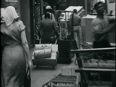 vídeos de stock, filmes e b-roll de black man pushing empty rolling rack on sidewalk w/ younger male pulling cart of packages behind male pushing two racks of clothing on street iconic... - 1963