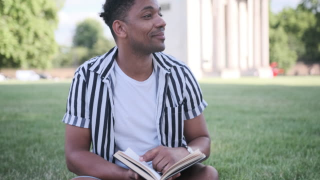 black man reading a book in the park in london in front of wellington arch - getting away from it all stock videos & royalty-free footage