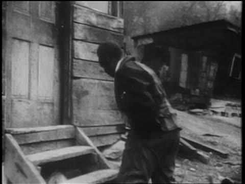 stockvideo's en b-roll-footage met b/w 1939 black man shooing away chickens + entering shack / documentary - grote depressie nieuwsevenement