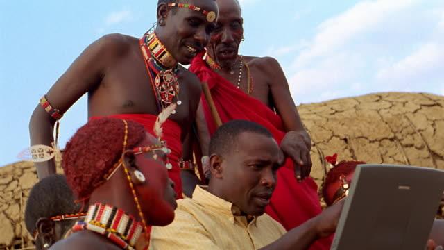 MS Black man showing laptop computer to Masai tribesmen / Kenya
