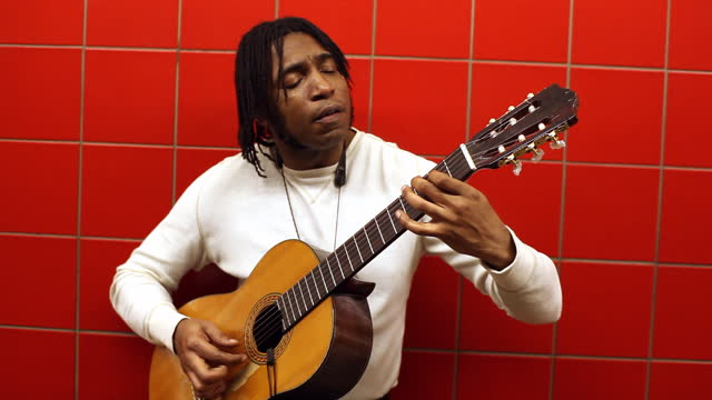 med black man sings   plays guitar while he leans against red wall in subway station - performer stock videos & royalty-free footage