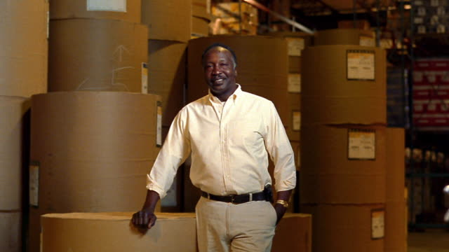 MS PORTRAIT Black man smiling standing in warehouse surrounded by rolls