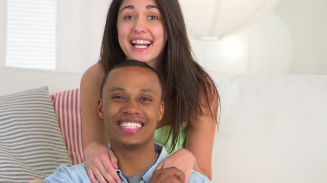 Black man smiling while girlfriend makes funny faces and sticks out tongue