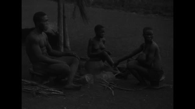 a black man smokes a pipe as a nursing woman and another attend to a campfire / pan of a walled settlement and huts with conical roofs / barebreasted... - bambina nuda video stock e b–roll