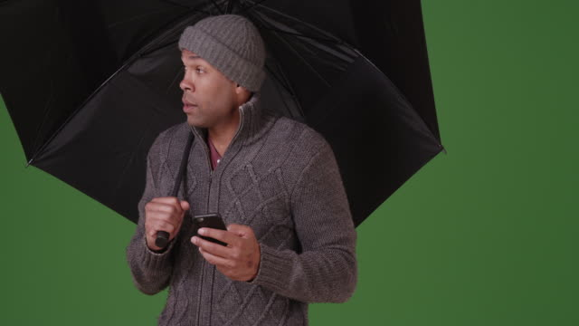 A black man stand with an umbrella on green screen