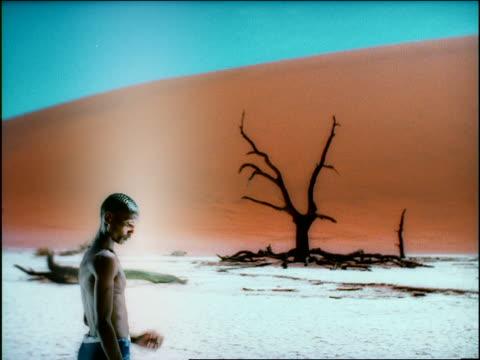 vídeos de stock e filmes b-roll de overexposed flash frames black man standing looking down in desert / dead tree in background - super exposto