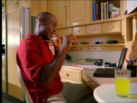 pan black man talking on phone + working on laptop computer in kitchen - landline phone stock videos & royalty-free footage