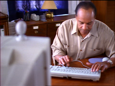 Black man typing with two fingers on computer in office