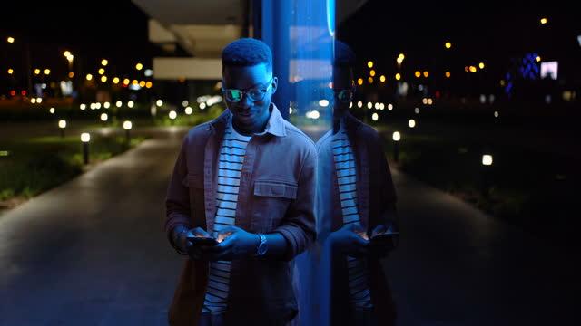 black man using phone on the street in the night - dark stock videos & royalty-free footage
