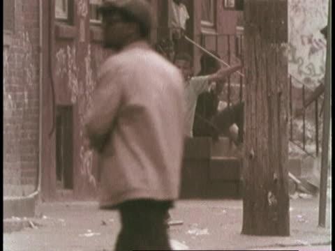 pan black man walking and sitting down on steps in philadelphia ghetto / united states - philadelphia pennsylvania bildbanksvideor och videomaterial från bakom kulisserna