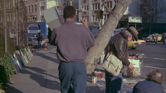 a black man walking down a new york city street carries a boombox on his shoulder. - shoulder ride woman stock videos & royalty-free footage