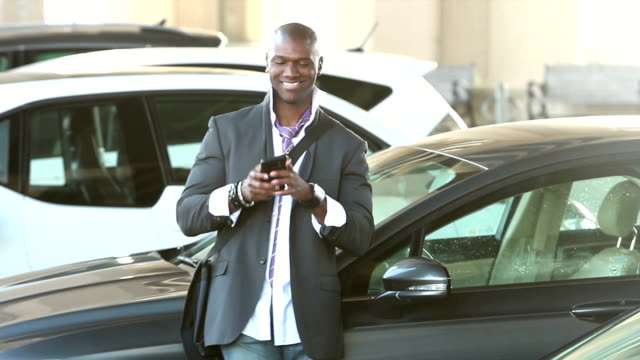 Black man walking thru parking lot looking at phone