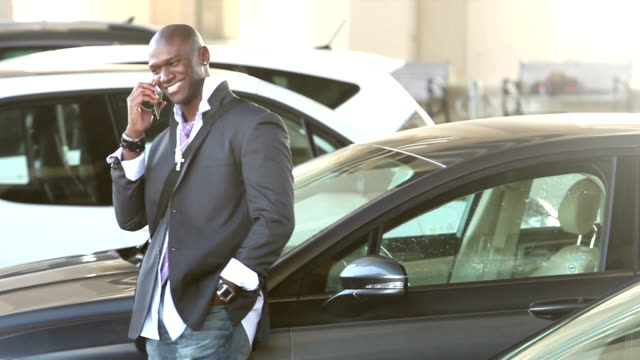 Black man walking thru parking lot talking on phone