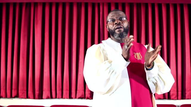 Black man wearing robe singing in church