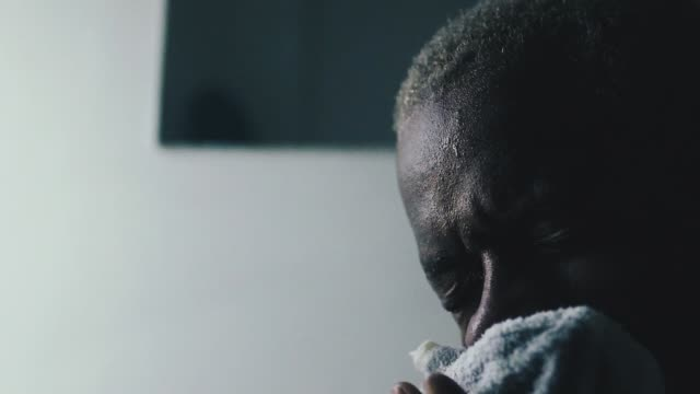 Black man wiping his face