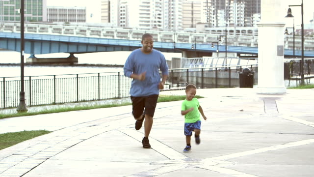 Black man with young son jogging in city park