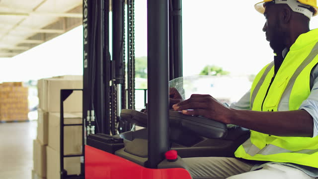 black man worker operating forklift in distribution warehouse. - commercial land vehicle stock videos & royalty-free footage