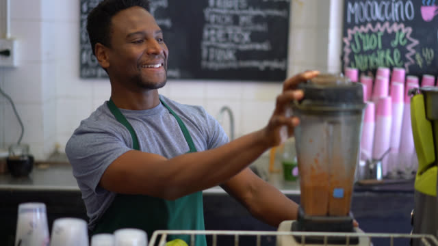 Black man working at a juice bar adding fruits to the blender to make a juice