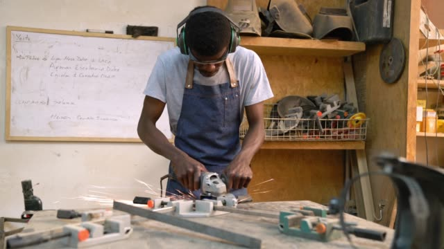 schwarzer mann, der in einer werkstatt arbeitet, um ein metallteil zu polieren, das sehr fokussiert aussieht - ohrenschützer stock-videos und b-roll-filmmaterial