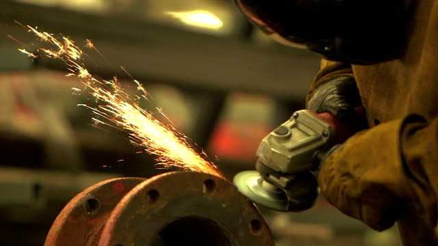 Black man working in factory, grinding metal pipe joint