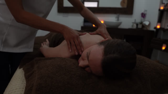 black masseuse giving a relaxing massage tom adult customer with dim lights while working - massage table stock videos & royalty-free footage