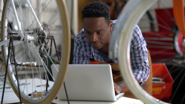 black mechanic at a bicycle repair shop taking a break and enjoying his social media on a laptop - owner stock videos and b-roll footage