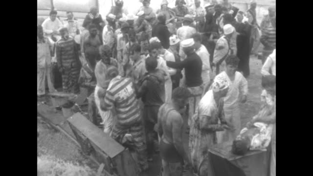 vídeos de stock e filmes b-roll de black men in grass skirts walk past during equatorcrossing ceremony aboard the uss maryland / vs men holding another on plank and others being dunked... - maça