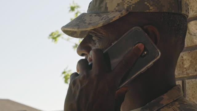 vidéos et rushes de black military man talking on cell phone - casquette