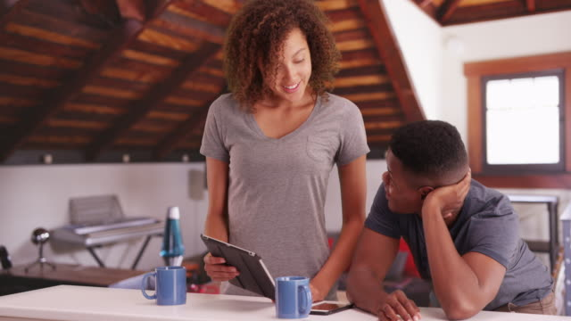 Black millennial couple discuss work and in their upscale loft