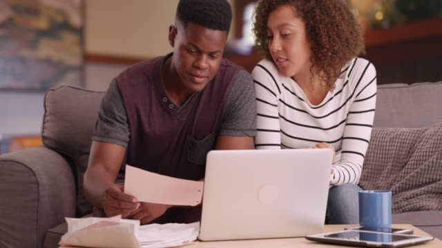 Black millennial couple paying bills with laptop computer in living room