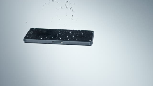 slo mo ld black mobile phone sinking into clear water and causing bubbles - sinking stock videos & royalty-free footage