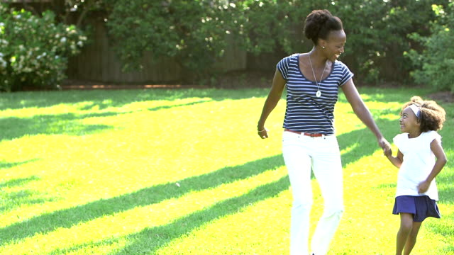black mother running, skipping, playing with little girl - skipping along stock videos & royalty-free footage
