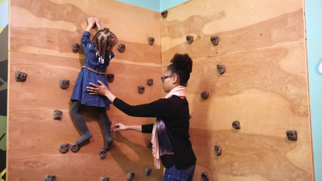 black mother watching daughter on climbing wall - kletterwand kletterausrüstung stock-videos und b-roll-filmmaterial