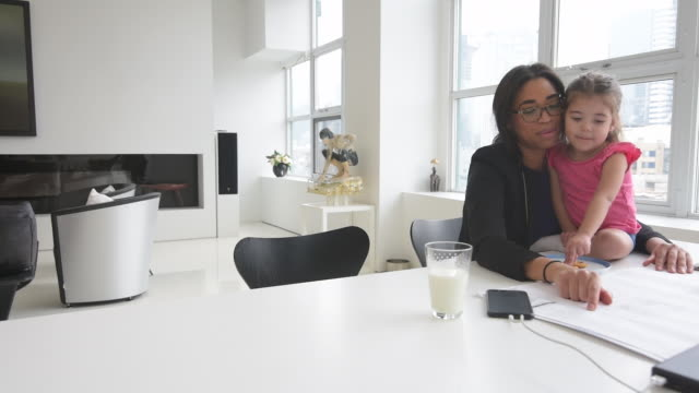 Black mother working in home office with daughter