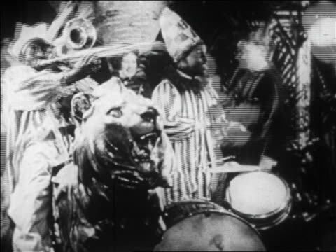 vidéos et rushes de b/w 1928 black musicains in clown costumes playing in nightclub / newsreel - 1928