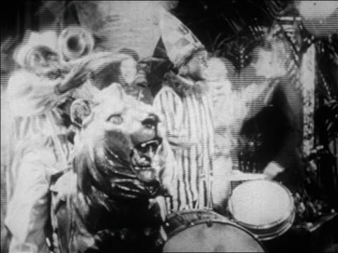 b/w 1928 black musicians in clown costume playing in jazz band in nightclub / newsreel - 1928 stock-videos und b-roll-filmmaterial