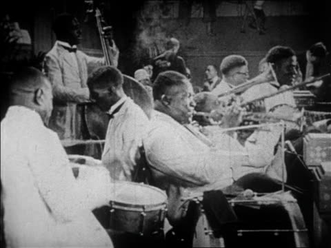 B/W 1928 Black musicians in white tuxedos playing in jazz band / newsreel