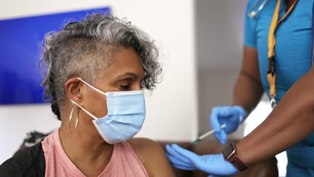 black nurse giving covid-19 vaccine to senior black woman - medical insurance stock videos & royalty-free footage