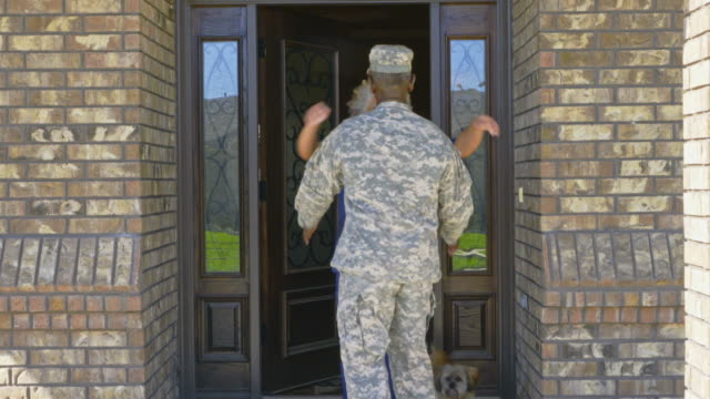 vídeos de stock e filmes b-roll de black nurse greeting military husband returning home from deployment - regresso ao lar