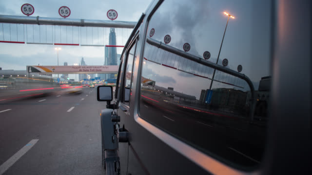 vidéos et rushes de black off road car driving at dawn on dubai's sheikh zayed road with the side of the car in foreground. streaking reflections in the car's surface and window, streaking city background. - tout terrain urbain