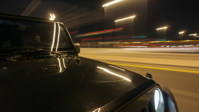 Black off road car driving at night from the countryside to Dubai city and through Palm Jumeirah tunnel. Hood in foreground. Streaking reflections on the car's surface and background.