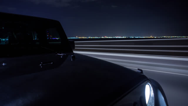 vidéos et rushes de black off road car driving at night on dubai's palm jumeirah island and through the palm jumeirah tunnel. hood in foreground. streaking reflections in the car's surface and background. - tout terrain urbain