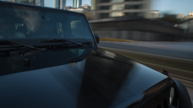 vidéos et rushes de black off road car driving during day through dubai city with the hood in foreground. reflections on the car's surface and streaking city background. - tout terrain urbain