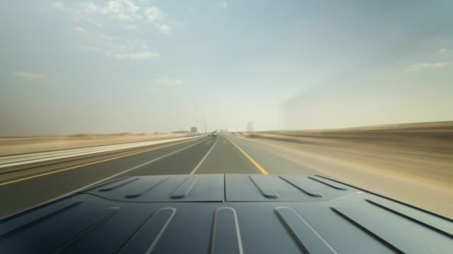 black off road car driving on a dubai highway and to dessert country roads. roof of the car in foreground. - zweispurige strecke stock-videos und b-roll-filmmaterial