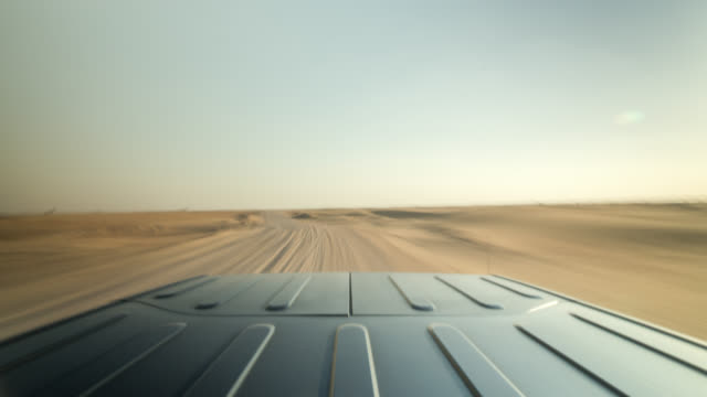 vídeos de stock, filmes e b-roll de black off road car driving on a rough dirt road through the sunny dubai dessert. roof of the car in foreground (camera mounted to the car in driving direction). - parélio