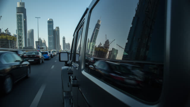 vidéos et rushes de black off road car driving on busy dubai streets during day with the side of the car in foreground. camera was mounted to the car in driving direction. streaking reflections in the car's surface and window. - tout terrain urbain