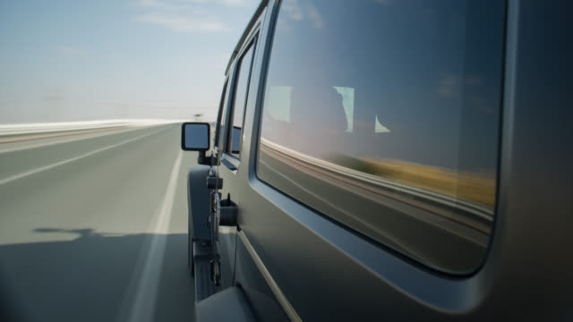 vidéos et rushes de black off road car driving outside dubai city with the side of the car in foreground. streaking reflections in the car's surface and window, streaking background. - tout terrain urbain